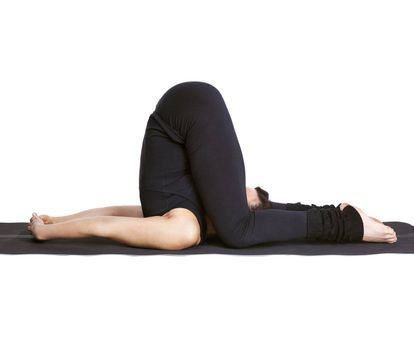 full-length portrait of beautiful woman working out yoga exercises karnapidasana pose on fitness mat