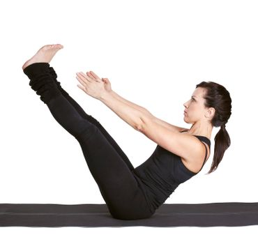 full-length portrait of beautiful woman working out yoga exercise paripurna navasana (full boat pose) on fitness mat
