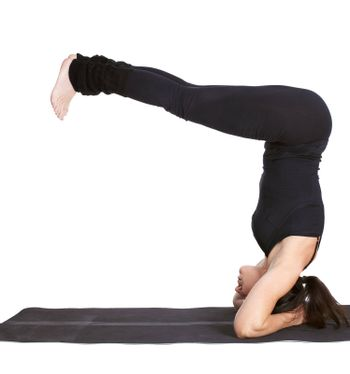 full-length portrait of beautiful woman working out yoga exercise salamba sirsasana (supported head stand) on fitness mat