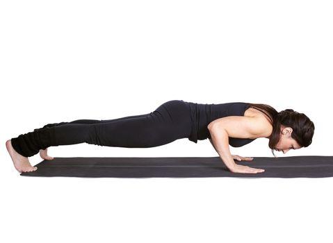 full-length portrait of beautiful woman pushing up on fitness mat in chaturanga dandasana pose