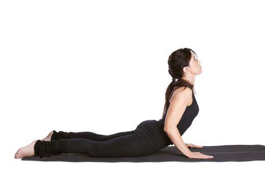 full-length portrait of beautiful woman working out yoga exercise bhujangasana (cobra pose) on fitness mat