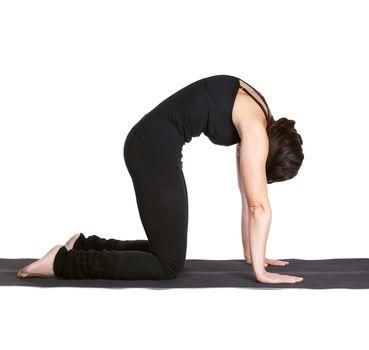 full-length portrait of beautiful woman working out yoga exercises mardzhariasana on fitness mat