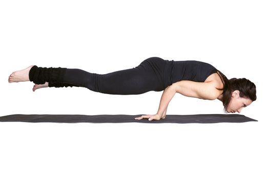 full-length portrait of beautiful woman working out yoga exercise balancing on hands on fitness mat