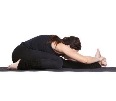 full-length portrait of beautiful woman working out yoga exercise janu sirsasana (head to knee forward bend) on fitness mat