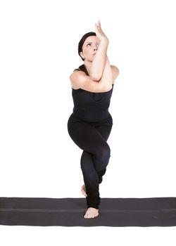 full-length portrait of beautiful woman working out yoga exercise garudasana (eagle pose) on fitness mat
