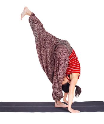 full-length portrait of beautiful woman strarting yoga exercise adho mukha vrksasana (hand stand) on fitness mat