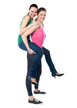 Teenage girl piggybacks her friend
