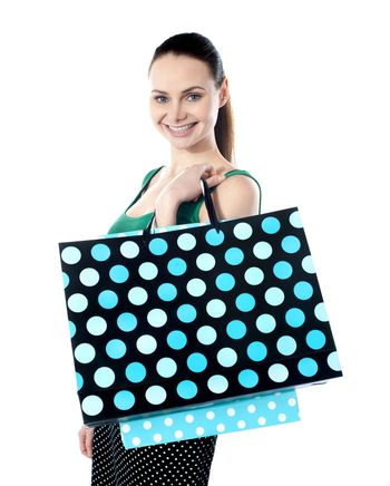 Glamorous smiling teenager shopping. Holding dotted bags