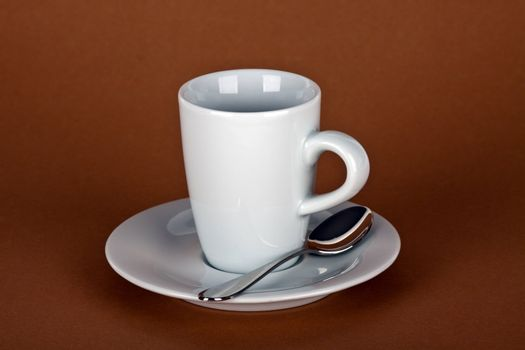 white coffe cup with coffe beans and a silver spoon