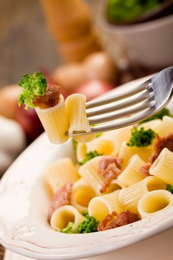 photo of delicious pasta with sausage and broccoli on wooden table