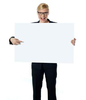 Saleswoman pointing at blank billboard