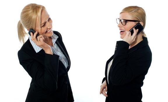 Businesswomen communicating via mobile phones