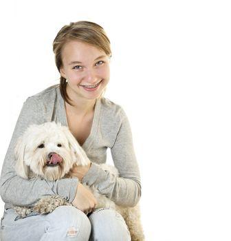 Pretty teenage girl holding adorable coton de tulear dog