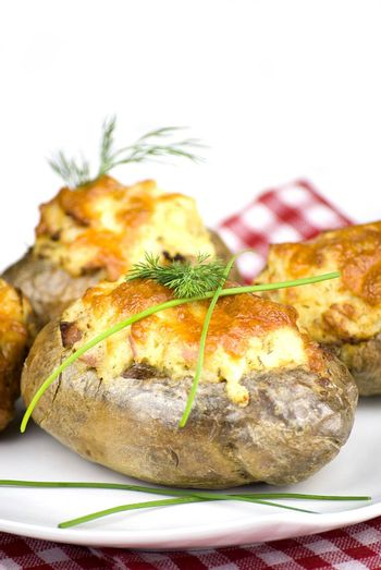 stuffed potatoes covered with cheddar cheese decorated with chives and dill leaves in a white plate