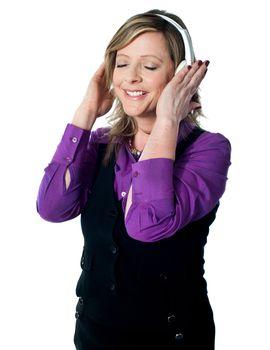 Senior lady enjoying music, lost deeply in it