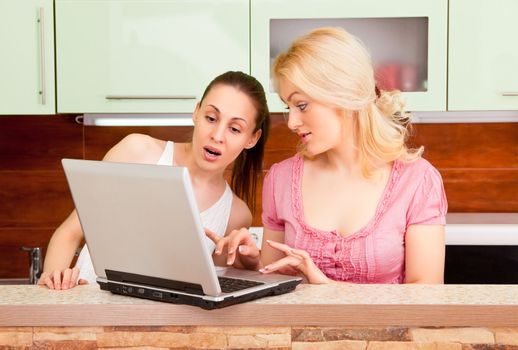 Two young women with a laptop in the kitchen