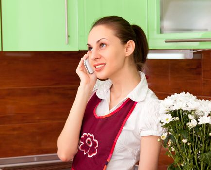 young housewife talking on the smartphone against the kitchen
