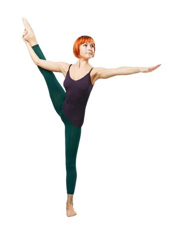 Slim beautiful woman practicing yoga asana standing on one foot