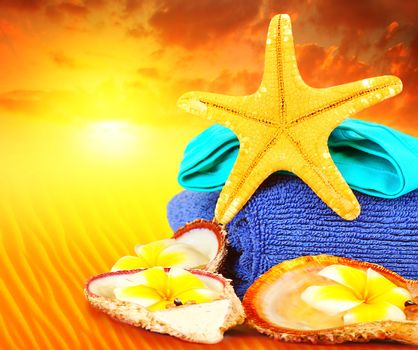 Beach items over sunset conceptual image of summertime vacation and holidays