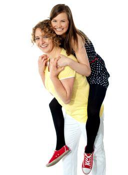 Teenage girl piggybacks her mother