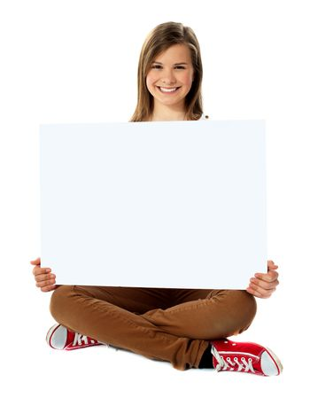 Smiling pretty teenager posing with blank placard
