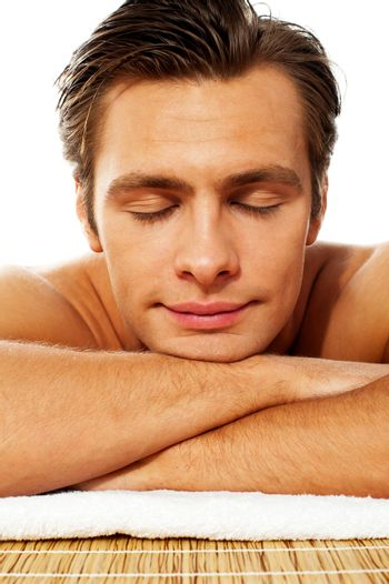 Attractive man resting with closed eyes at spa