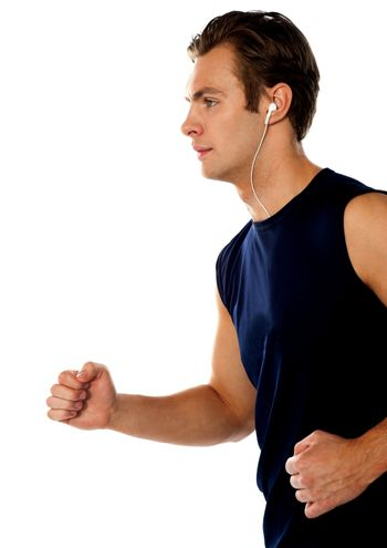 Fit athlete enjoying music in a jogging posture