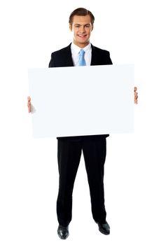 Portrait of businessman showing blank signboard