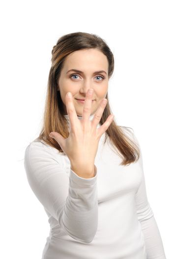 Young attractive girl shows gesture of the figure five. Isolated on white.
