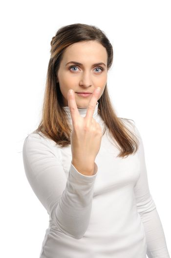 Young attractive girl shows gesture of the figure two. Isolated on white.