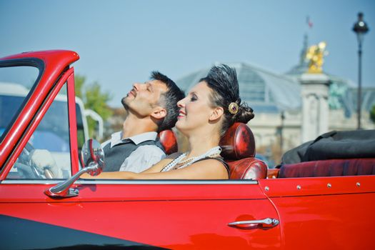 Young happy couple in retro-style travel in a car in Paris