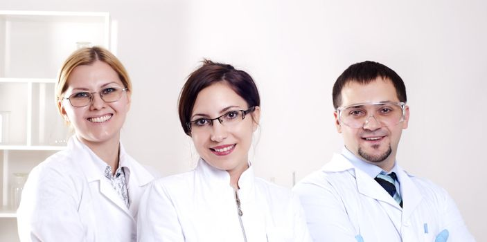 Three doctors are smiling at the camera in a doctors' office. Horizontally framed shot.