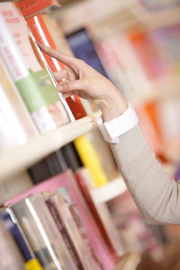 young woman looking for a book in a bookstore - hand close up