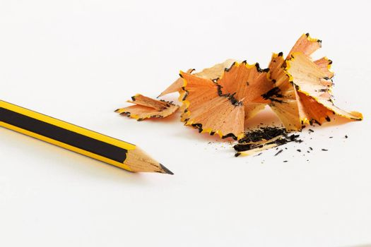 Sharpened pencil and wood shavings on white background