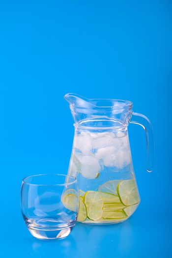 Lemonade Pitcher with ice on blue background
