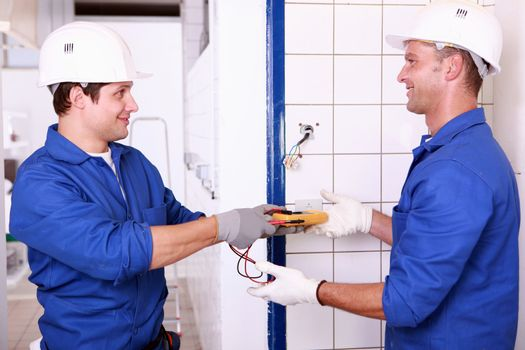 Two male electrical engineers  checking power supply