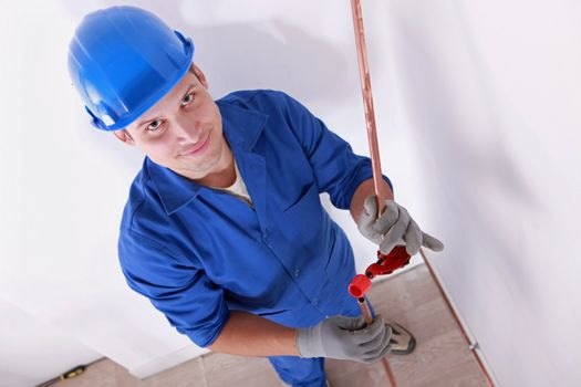 Smiling laborer installing piping