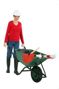 Woman pushing a wheelbarrow containing her tools