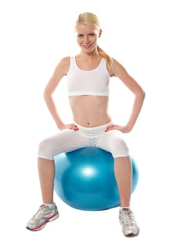 Gorgeous teenager sitting on exercise ball