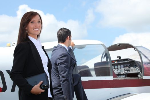 Businesspeople next to airplane