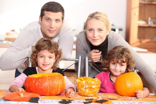 A family carving Halloween pumpkins.