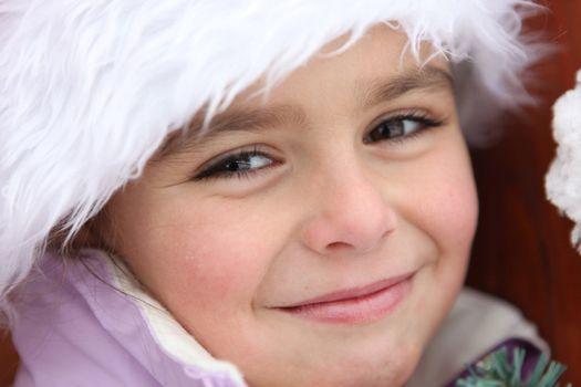 Portrait of a cute little girl by wintertime