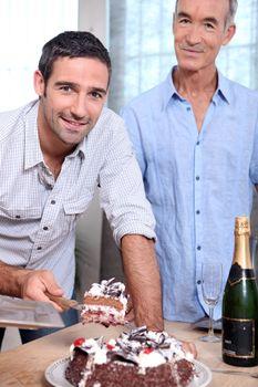 Two men cutting celebration cake