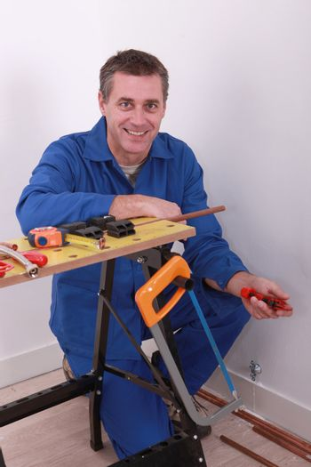 Plumber with tools and copper piping