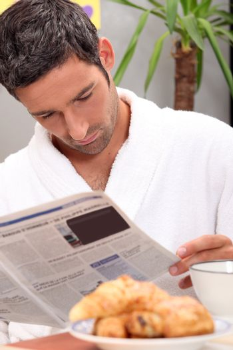 Man reading a journal over breakfast