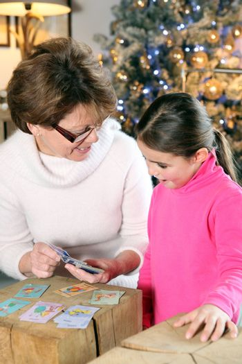 Grandmother and child playing cards at Christmas