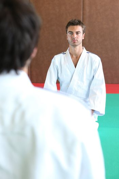 Two men kneeling on a judo mat