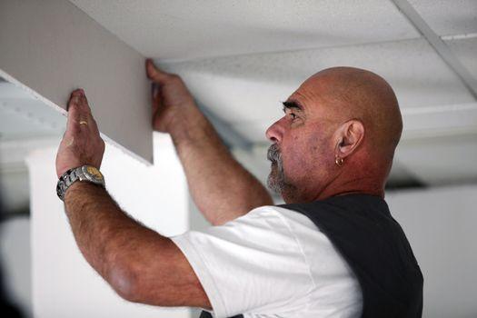Tradesman installing drywall