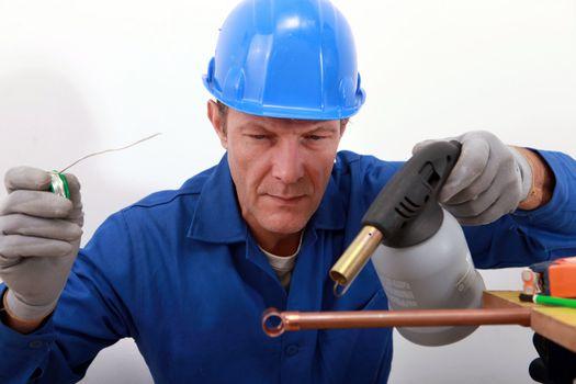 craftsman soldering a copper pipe