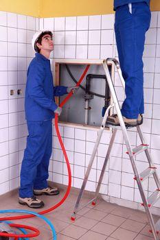 Two plumber fixing bathroom water supply